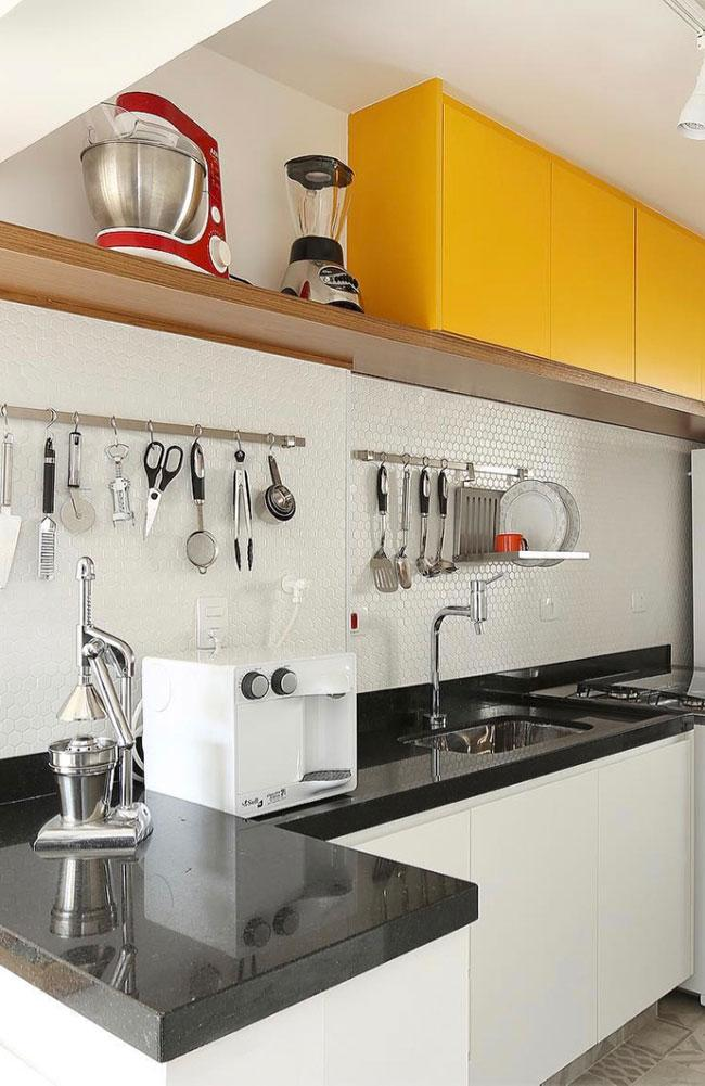 White furniture with black stone in this kitchen design
