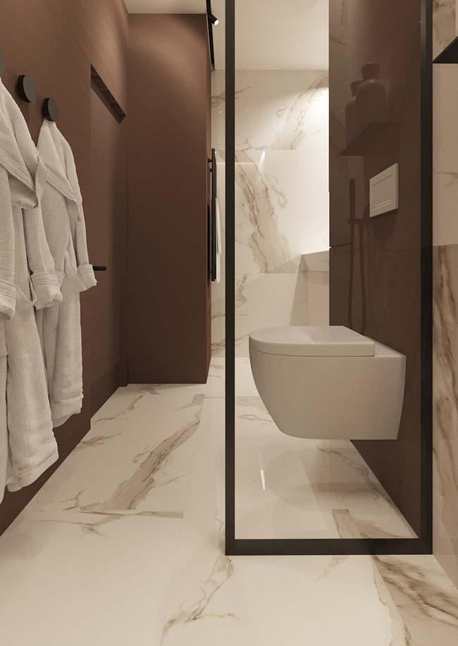 Marble Calacatta Oro contrasting with the earthy tone of the bathroom wall
