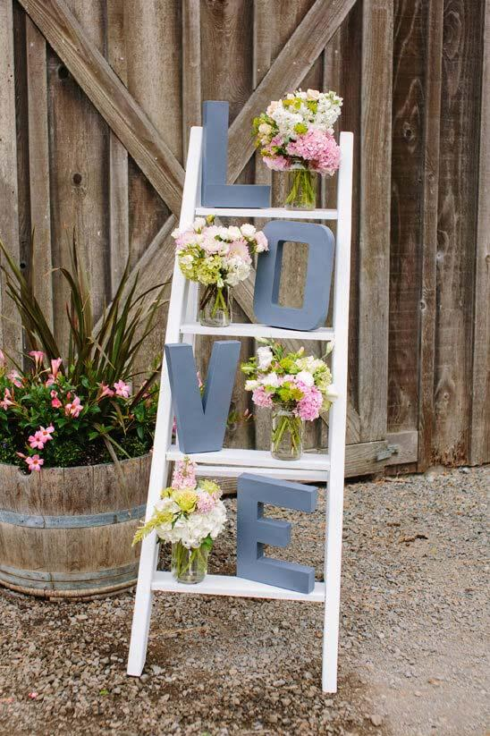 Simple engagement party: wooden staircase decorated with the word love and vases