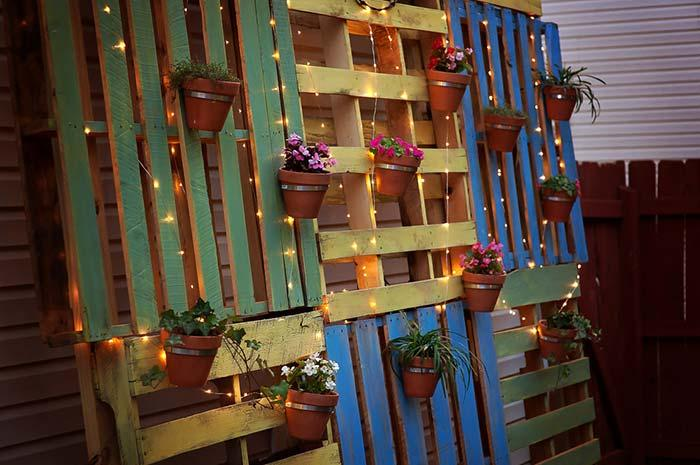 Colorful pallets recumbent in the wall supporting the pots of plants