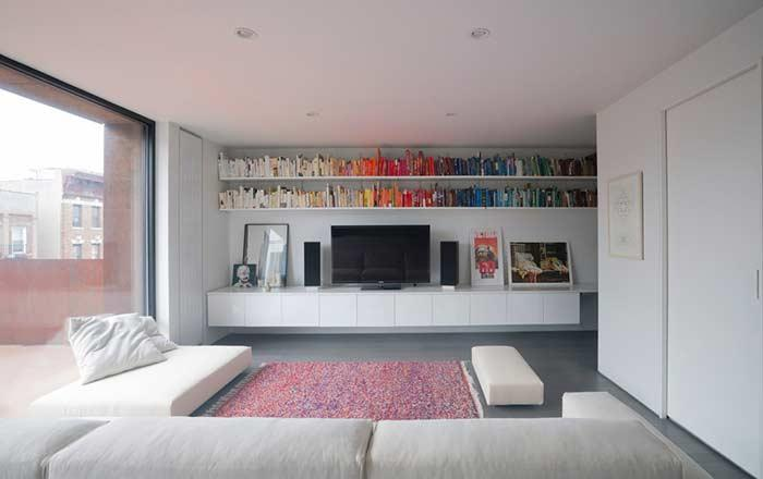 TV room with shelves at the top of the wall: here the choice is made by the organization by colors.