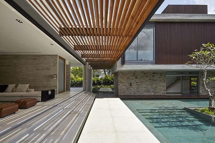 White porcelain tile and wooden deck line the pool area