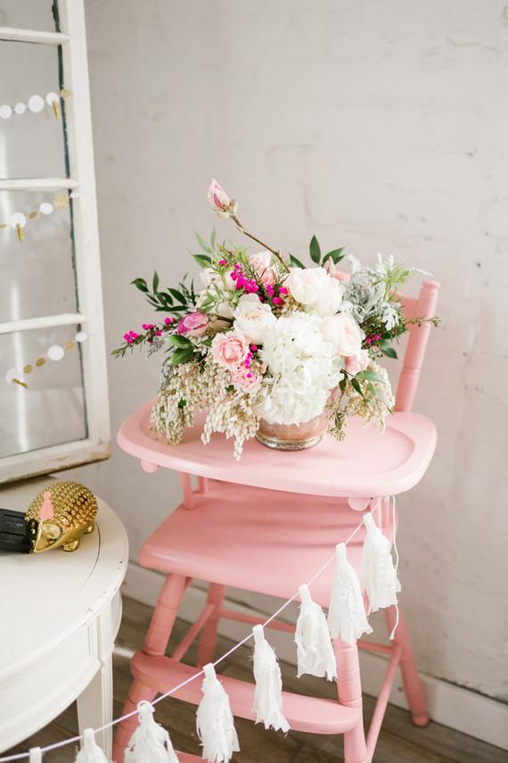 Arrangement of flowers decorates the baby highchair