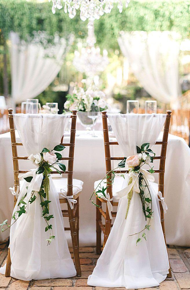 Do-it-yourself wedding decoration: wedding party chairs decorated with voil and flowers