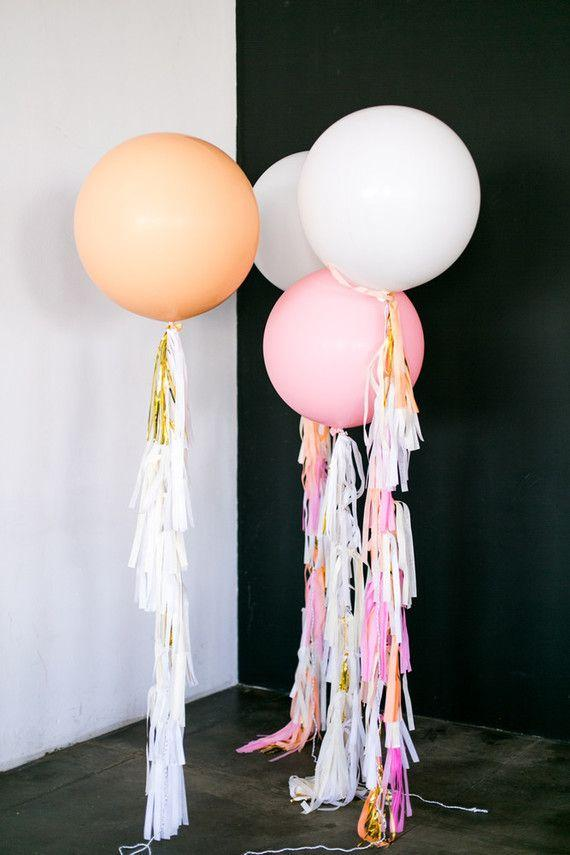 Balloons pinned to the floor with colorful ribbons
