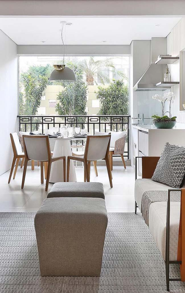 Clean light-colored decoration encompasses the living room, dining room and balcony of this decorated apartment
