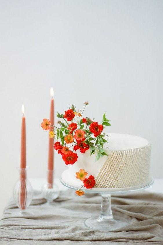 Simple wedding cake with whipped cream and red flowers