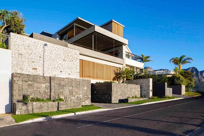 Gabions of stone and concrete form retaining walls around the house