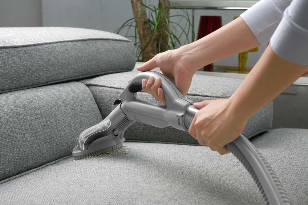 Vacuum cleaner on fabric sofa