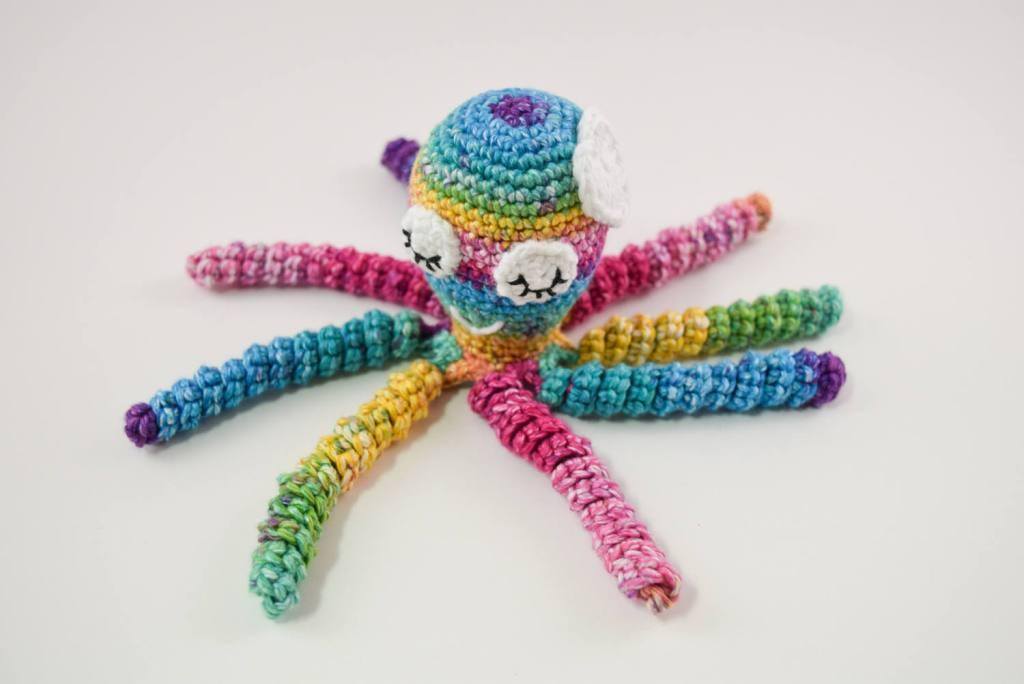 Colorful crochet octopus with a white flower on the head