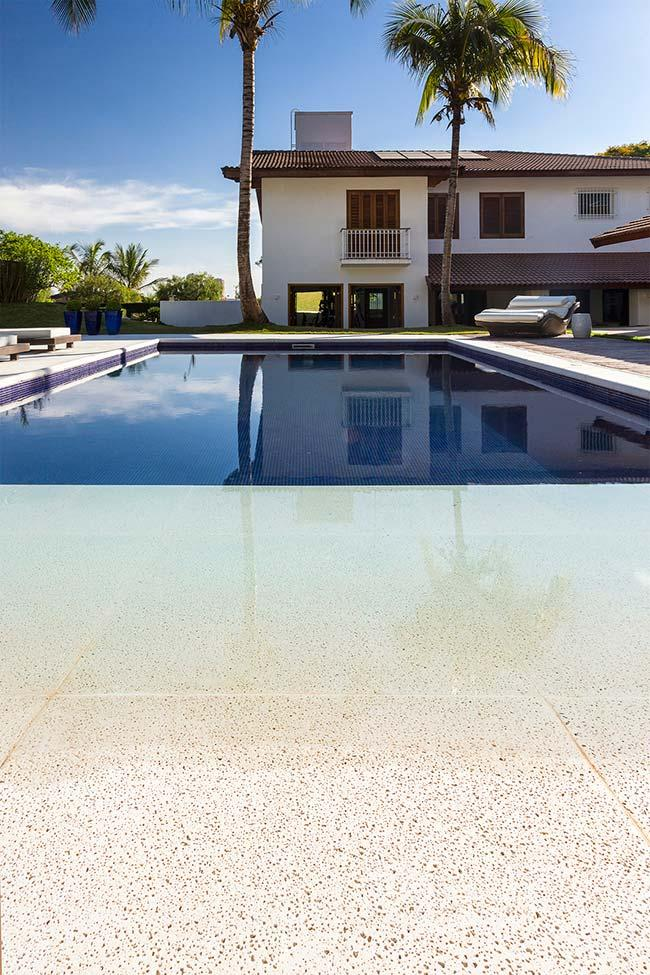 Stone swimming pool floor with small black dots